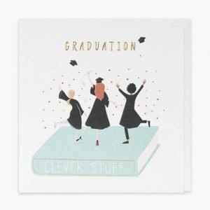 A lovely graduation card with gold foil and embossed details. A drawing of 3 graduates throwing their hats in the air dancing on a big book and the words Graduation