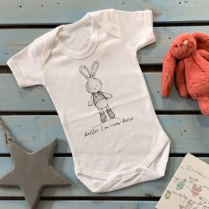 A white soft cotton baby vest with a lovely grey print bunny design with the words Hello I'm new here printed on it