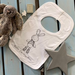 A white soft cotton baby bib with a lovely grey print bunny design with the words Hello I'm new here printed on i