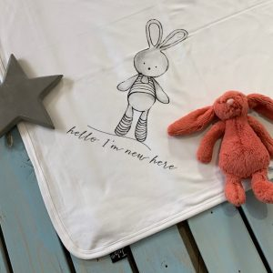 A white soft cotton baby blanket with a lovely grey print bunny design with the words Hello I'm new here printed on it