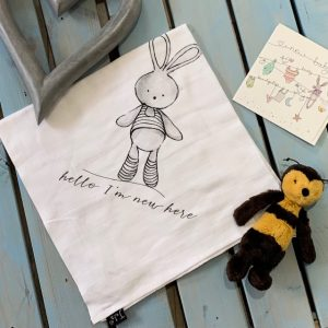 A white muslin cloth with an image of a cute grey bunny with the words Hello I'm New Here printed on it.