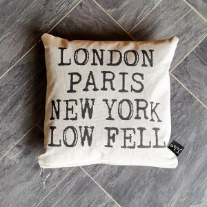 A hand made square cushion with a feather filled inner and a natural linen cover that is printed with London Paris New York Low Fell