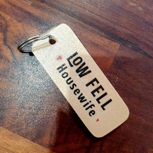 A wooden key ring printed with Low Fell Housewife