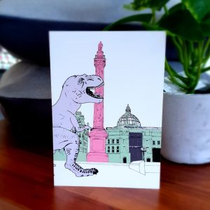 A contemporary greetings card with a drawing of the Earl Grey Monument in Newcastle upon Tyne with a casual T Rex dinosaur strolling by!