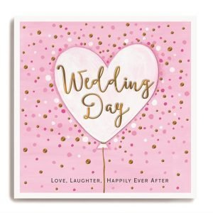 A square card with a pink spotty background. In the centre of the card is a large pink heart shaped balloon with the words Wedding day embossed and printed in gold shimmer effect. At the bottom of the card are the words 'Love Laughter Happy Ever After.