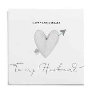 A white square card with a grey heart with an arrow through it which is finished off with little diamante on it. The Words Happy Anniversary to my husband is also printed on it.