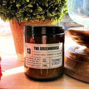 A candle in a brown glass apothecary jar. 40 hour burn time. Ripe tomatoes on the vine and deep red rhubard sitting on a heart of earthy sage