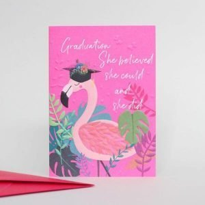 A pink graduation card with a flamingo in a mortar board and colourful leaves and the words Graduation She Believed She Could And She Did