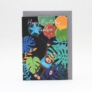 A Grandson birthday card in neon bright colours. Tropical leaves in blues on a dark background with a cheeky monkey hanging onto balloons in the foreground. He is wearing a t-shirt with cheeky on it. The wording is happy birthday grandson