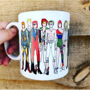 A white mug with images of David Bowie and his varied fashion styles
