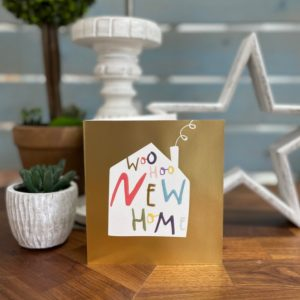 A gold foil effect card with an image of a house with colourful hand written style text inside of it.