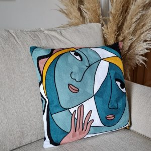 A modernist style cushion with faces. In beautiful greens with splashes of mustard, white and taupe. Outlined in black. the geometric abstract design is embroidered. The cushion has a zip fastening and a dark navy cotton canvas backing