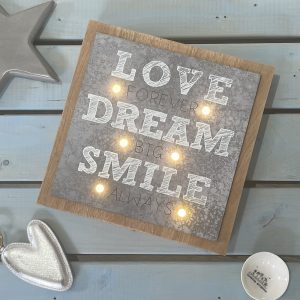 A square light up sign with a metal plaque printed with Love Forever, Dream Big Smile Always with 6 LED lights. Surrounded by a dark wood frame