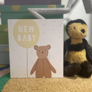 A new baby card with a picture of a teddy bear holding a yellow balloon with New Baby written on it in white. The background has grey spots