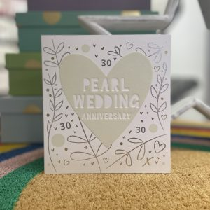 A pearl wedding 30th wedding anniversary card with a big pearl heart , hand drawn branches, hearts and 30's . The words Pearl Wedding Anniversary are in white inside the heart