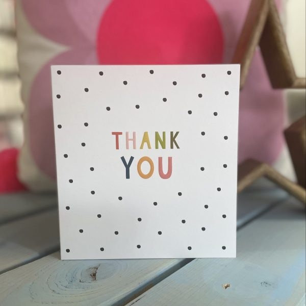 A white card with black spots and Thank you in colourful lettering