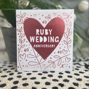 A ruby wedding 40th wedding anniversary card with a big ruby heart , hand drawn branches, hearts and 40's . The words Ruby Wedding Anniversary are in white inside the heart