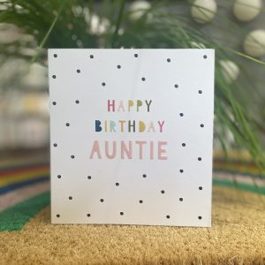 A spotty birthday card with happy birthday auntie in multi coloured lettering