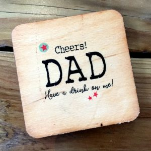 A wooden coaster with the words Cheers Dad Have a drink on me printed on it.
