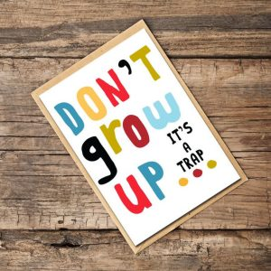 A white card with the words 'Don't grow up its a trap printed in colourful lettering