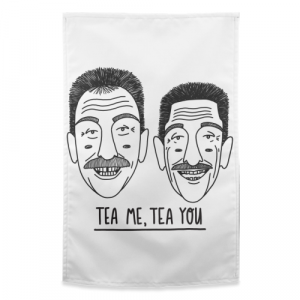 A white teatowel with an image of the Chuckle Brothers and the words Tea Me Tea You printed on it.