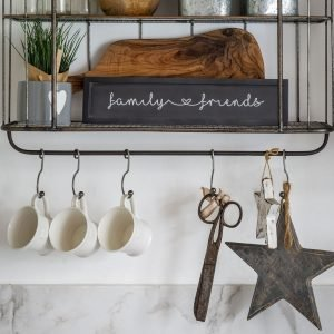 A black wooden sign with a black frame and white caligraphy reading family and friends